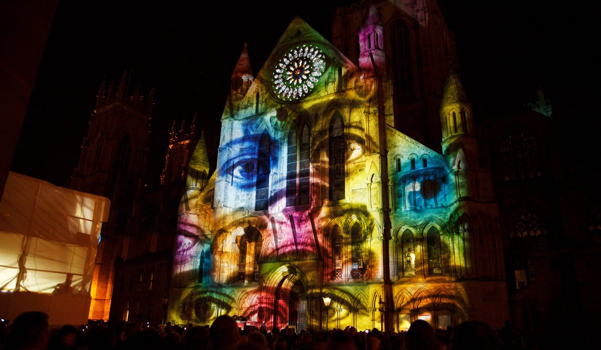 3D projection mapping execution - multi-color visuals of faces projected on an old building