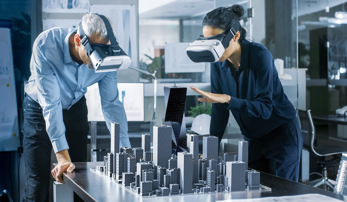 2 professionals in office setting looking at 3D model of a building with the assistance of Virtual Reality technology